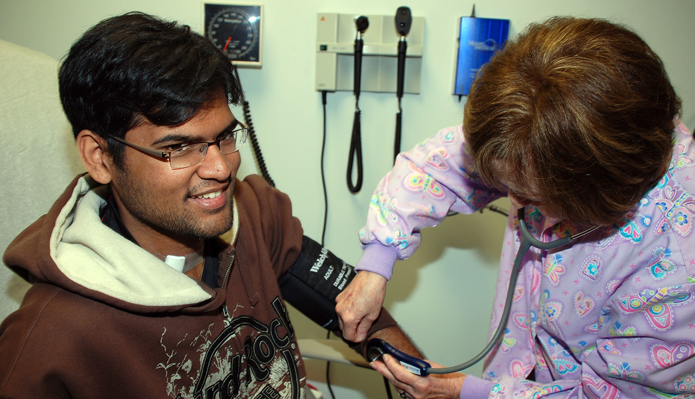 A male student gets his blood pressure checked at Student Health Services.