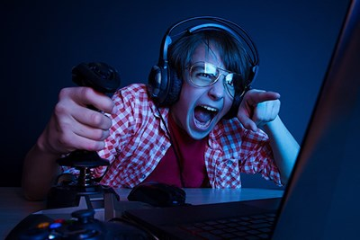 Teen wearing headphones excitedly playing video games