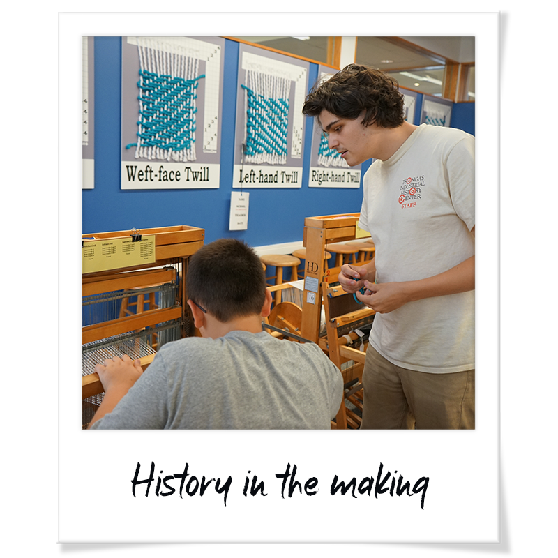 """Polaroid"" photo of Bradley Sherwood teaching a student how to weave on a loom at a Tsongas Industrial History Center summer camp - handwriting on frame reads ""History in the making"""