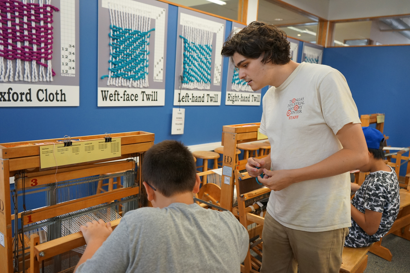 Bradley Sherwood helps a child weave on a loom at summer camp at the Tsongas Industrial History Center