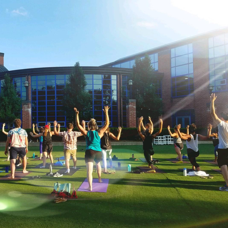 Students participate in an outdoor yoga class on the lawn of the Campus Recreation Center on a sunny afternoon