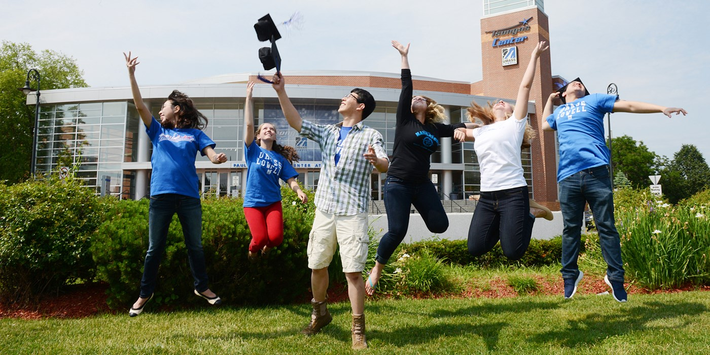 Six UMass Lowell students jump for joy in front of the Tsongas Center at UMass Lowell