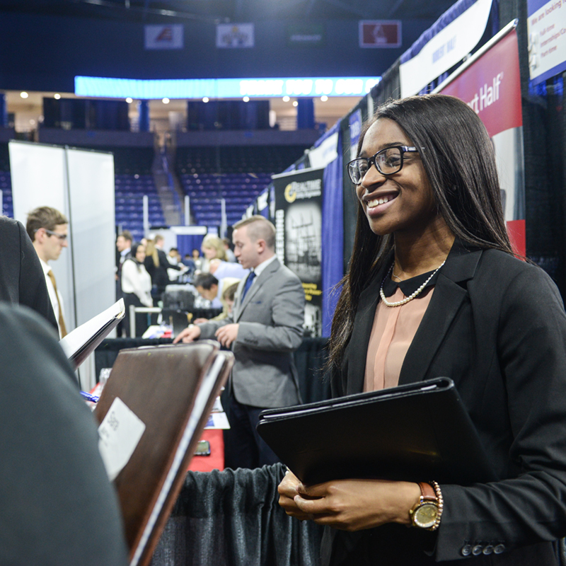 A female student smiles at the Career Fair