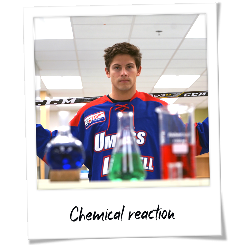 """Polaroid"" shot of Charlie Levesque wearing his River Hawks hockey uniform holding a hockey stick in a chemistry lab - handwriting on frame reads ""Chemical reaction"""
