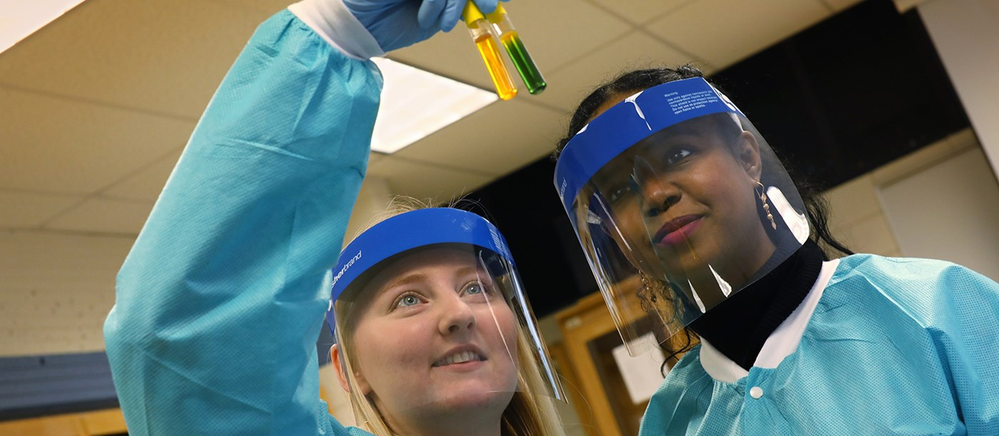 Two female students in protective gear look at test tubes of liquid