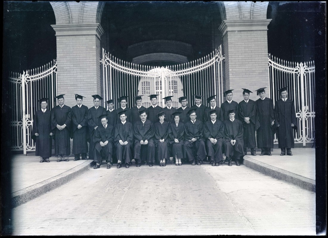 Graduates from the class of 1930 pose for a photo in caps and gowns outside the gates of Southwick Hall on North Campus
