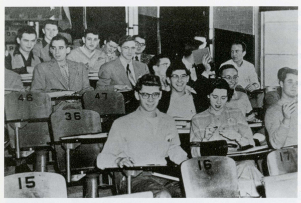 Students sit in a lecture hall in the 1950s in wooden numbered chairs