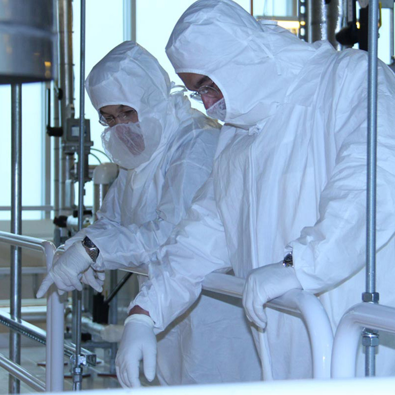 Two white-suited men working in clean room