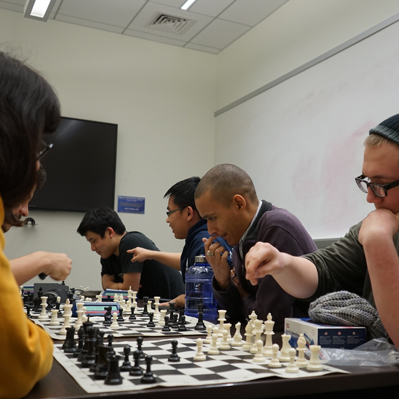 A group of students plays chess in the Club Hub at UML