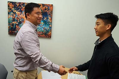 Alum Wentao Wang shakes hands with a student applying for a Pfizer co-op