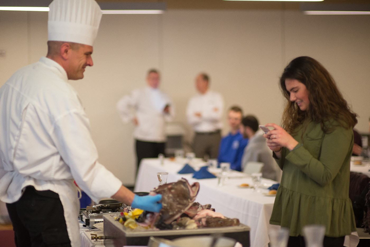 A UMass Lowell student takes a photo of executive chef Frank Hurley posing with a monkfish at a cooking class