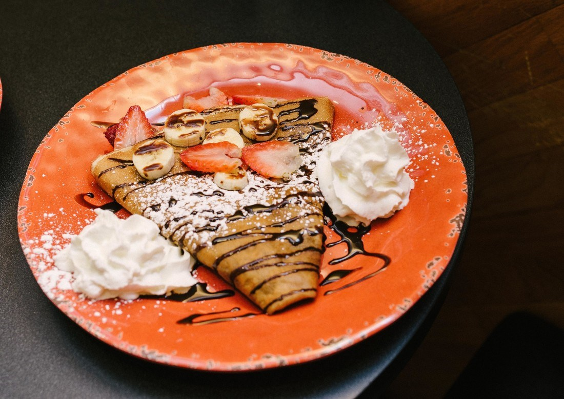 A crispy crepe on an orange plate drizzled with chocolate and topped with bananas, strawberries and whipped cream