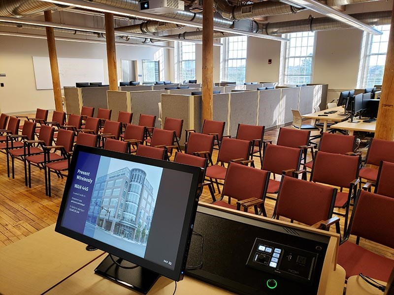 Rows of chairs face a presentation podium with banks of computers behind
