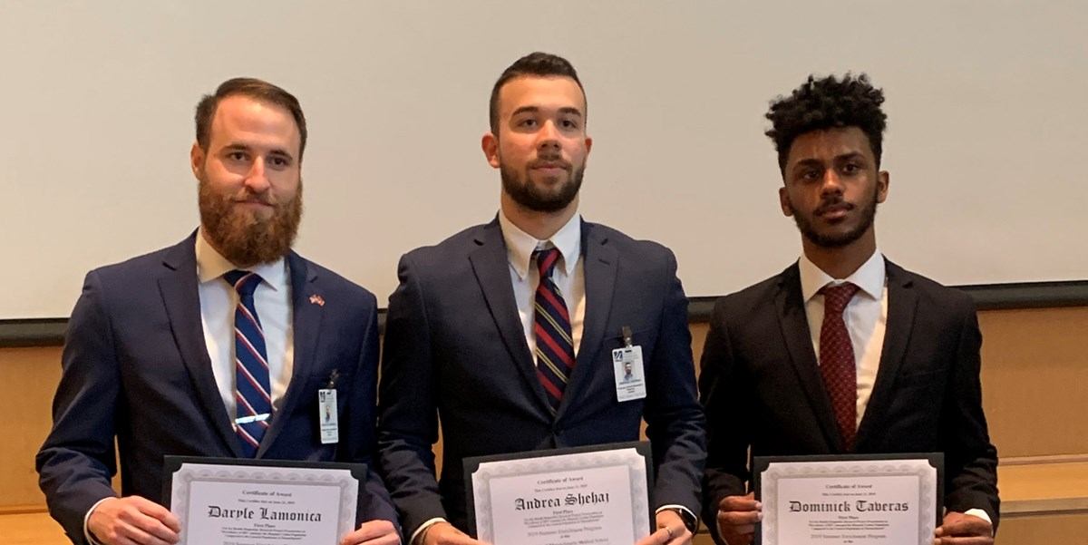 Daryle Lamonica stands with two other students, all in suits, holding certificates for completing a summer enrichment program