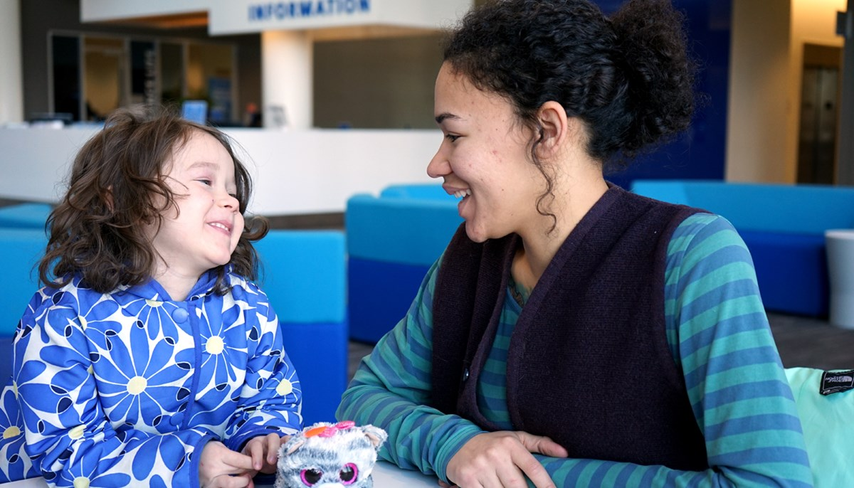 UMass Lowell student Denia Taylor sitting at a table at University Crossing with her daughter