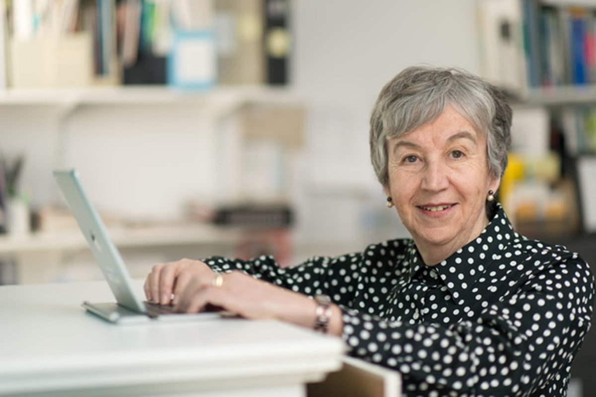 Diane Feeney Mahoney works at a laptop at a desk in a bright, white office