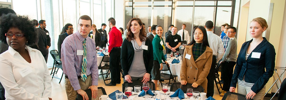Students wait behind their chairs at the UML Dine & Dress, hosted annually by the Career & Co-op Center.