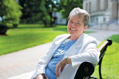 Alum Dotty Boivert sits on a bench outside Coburn Hall at UMass Lowell
