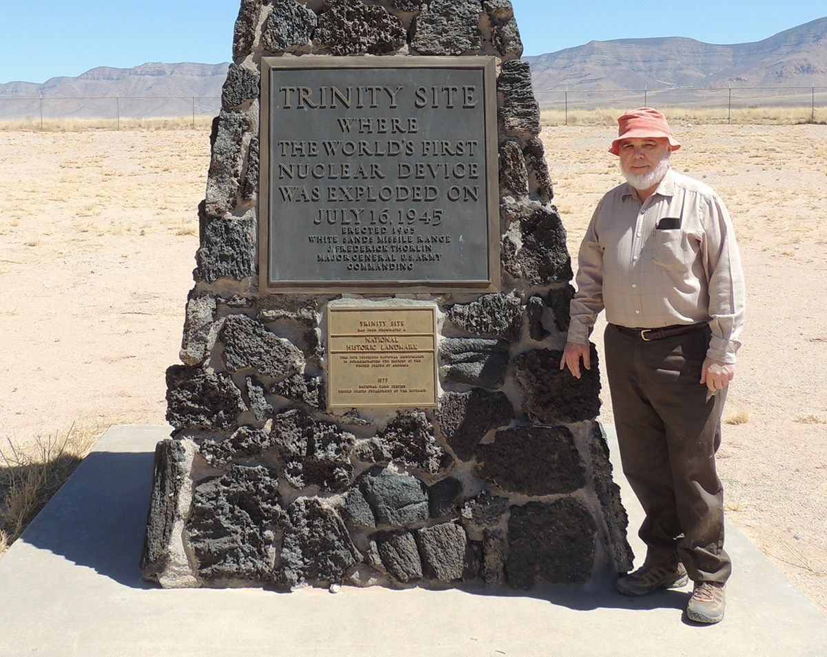Professor Nelson Eby poses next to the Trinity Site monument. Eby's general area of research is geochemistry. Recent projects - characterizing the glass (Trintite) produced during the first atomic bomb test; petrology and geochemistry of Jurassic - Cretaceous magmatism in the northeastern US and Canada; petrology and geochemistry of the Chilwa Alkaline Province, Malawi; origin of the Franklin and Sterling Hill ore deposits; F and Cl in apatite, amphibole, and biotite; using tree-ring cores to map environmental change; and source and distribution of atmospheric pollutants.