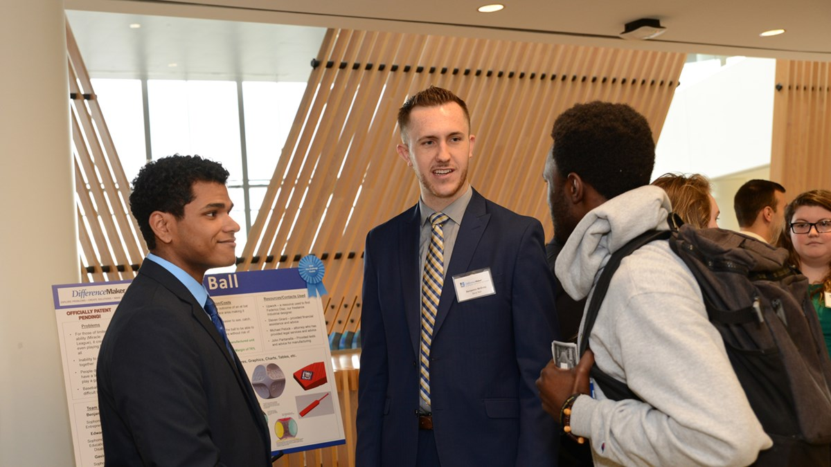 Edward Morante (left) stands with Benjamin McEvoy in front of their poster at a DifferenceMaker event, talking to a student