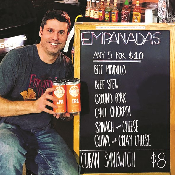 A man holds up cans of IPA in front of the chalkboard menu at Empanada Dada