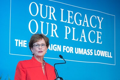 UMass Lowell Chancellor Jacquie Moloney in front of Our Legacy, Our Place banner