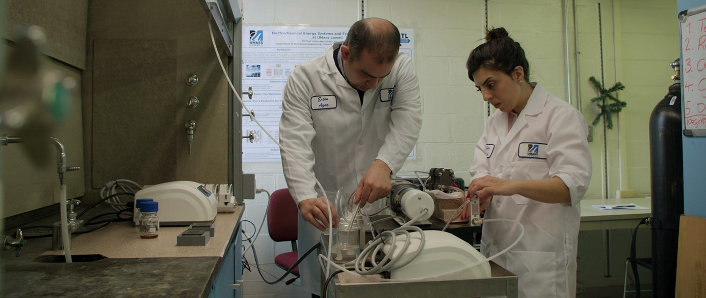 Two energy storage researchers working in a lab at UMass Lowell.
