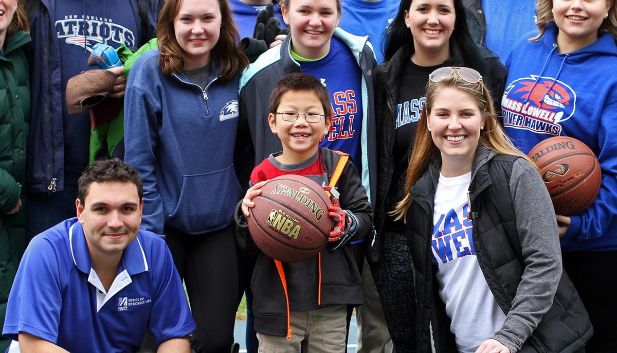 Child with prosthetic hand holding a basketball surrounded by students