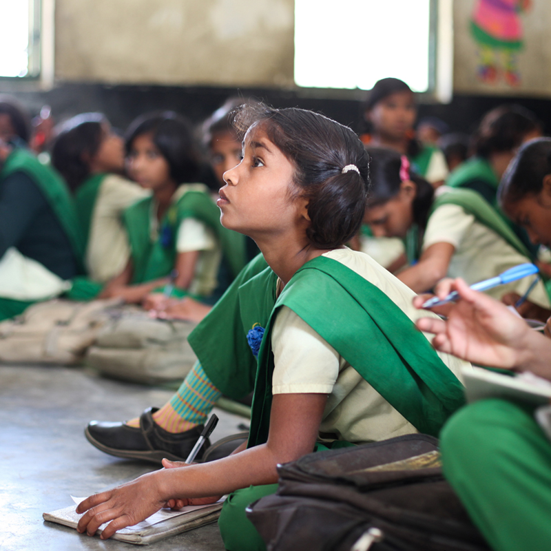 A young girl attentively listens at a free school for girls in the town of Anupshahr called Pardada Pardadi