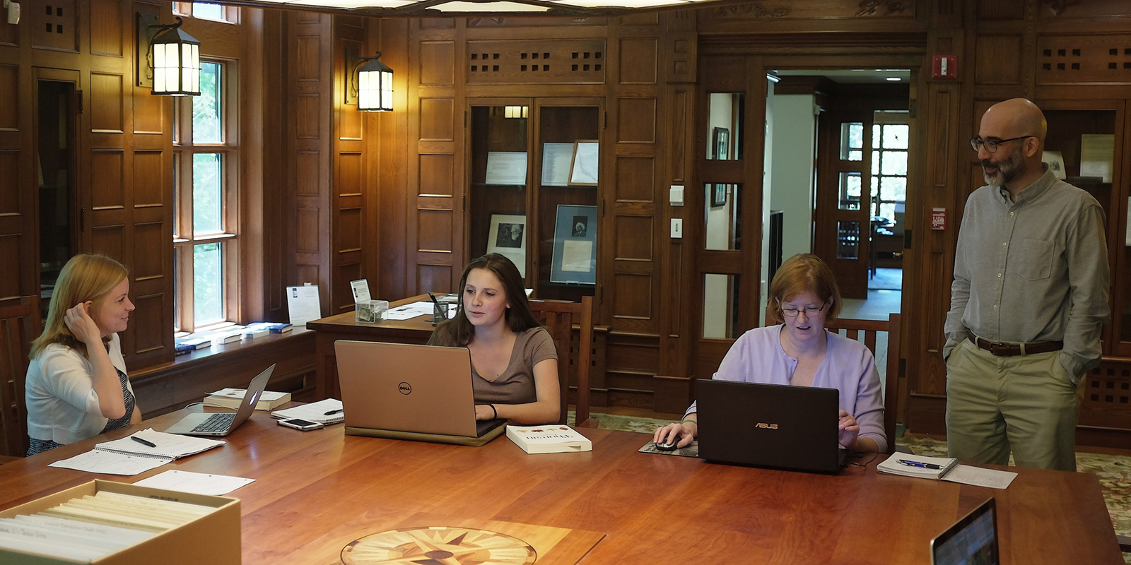 Honors College students Lindsay Blount, Kale Connerty and Erin Monahan work at the Thoreau Institute library with curator Jeffrey S. Cramer.