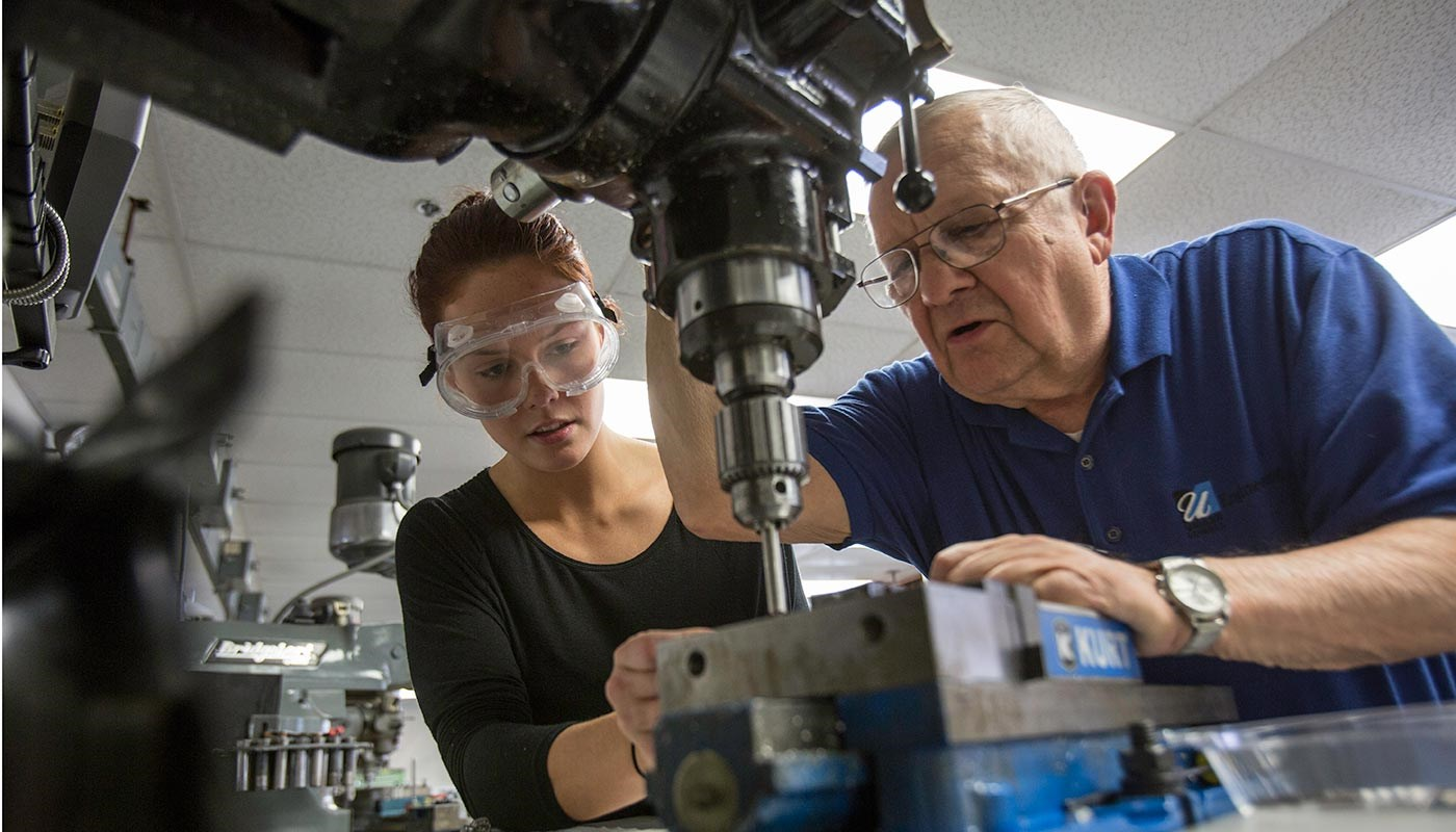 Female student works with male faculty member in lab