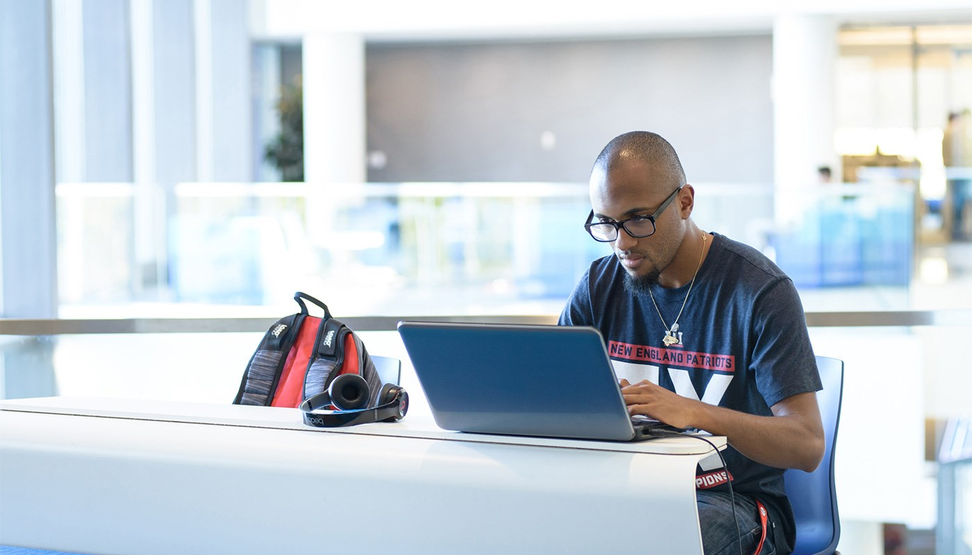 Balding young black man working on laptop