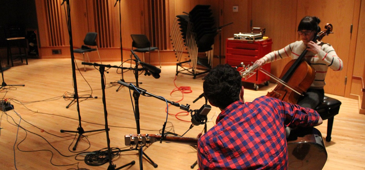 A female and male student playing instruments int he studio and recording music.