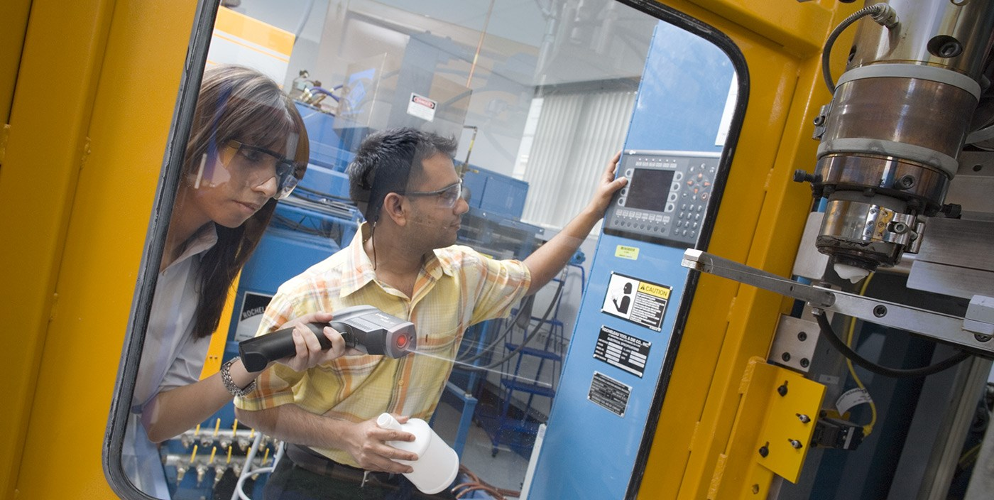 A female and male UMass Lowell student seen through the window of  the Blow Molding machine