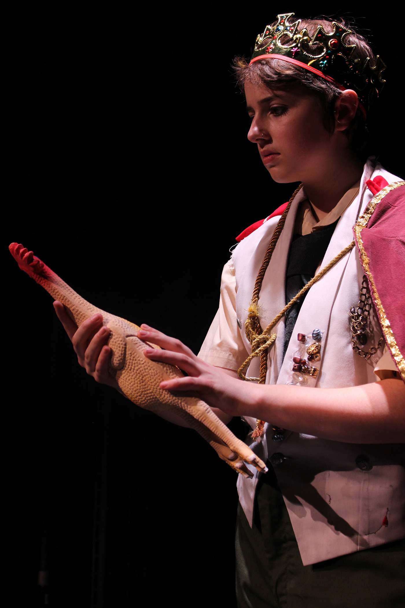 A female student wearing a crown and holding a rubber chicken on stage during a UMass Lowell Theatre Arts production.