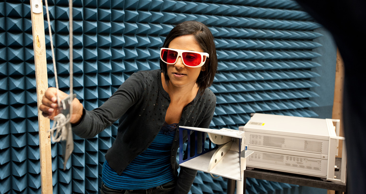 A female UMass Lowell student wearing goggles and working in a Civil & Environmental Engineering lab or class.