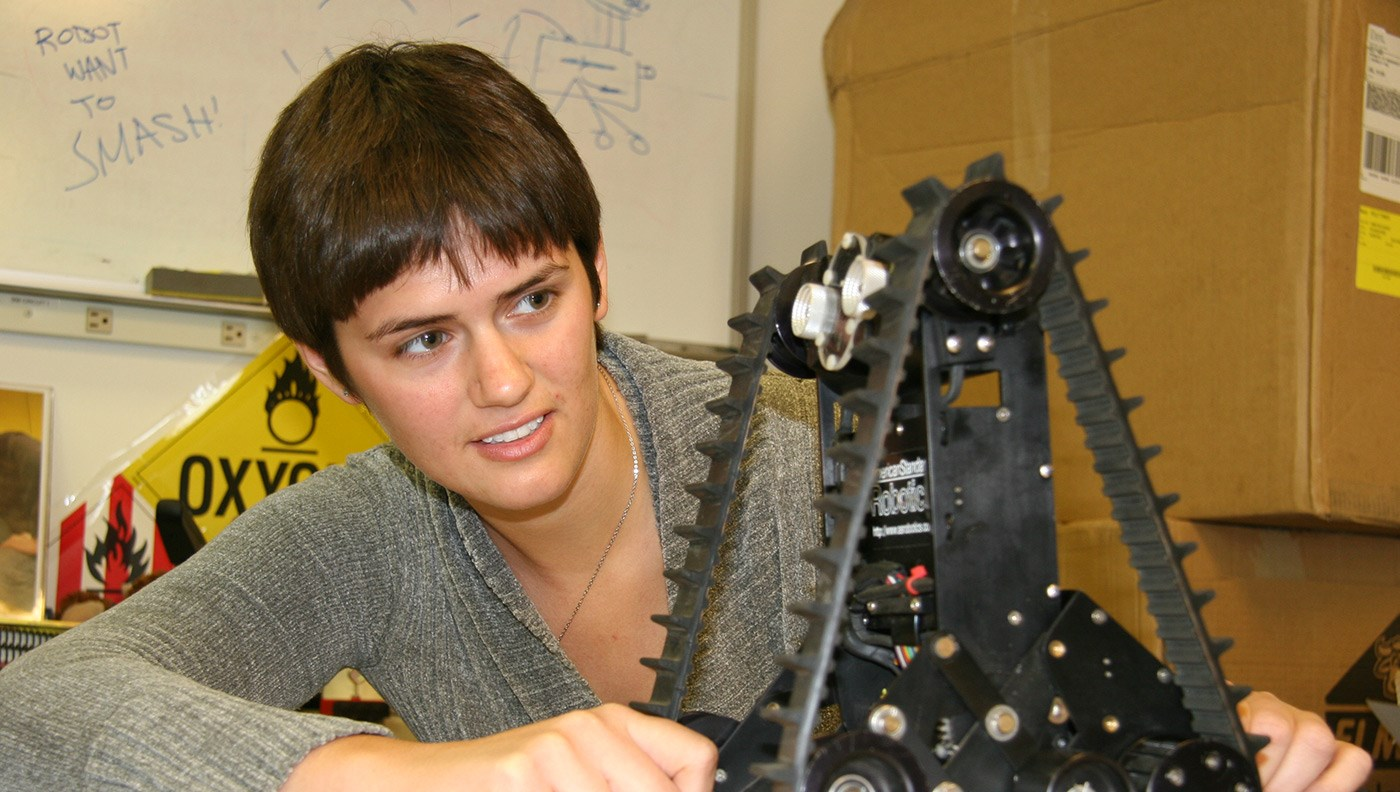 female-student-looking-at-treaded-robot-cs-robotics