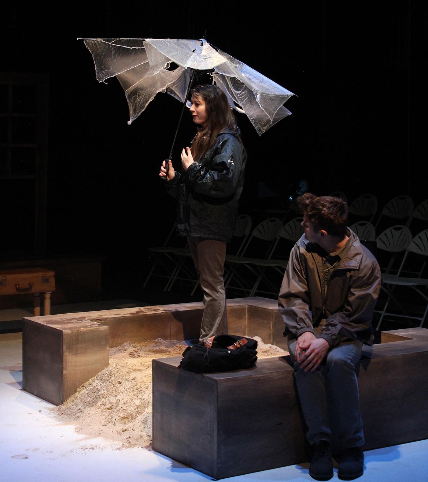 A female holding an umbrella on stage while a male student looks on during a UMass Lowell Theatre Arts production.