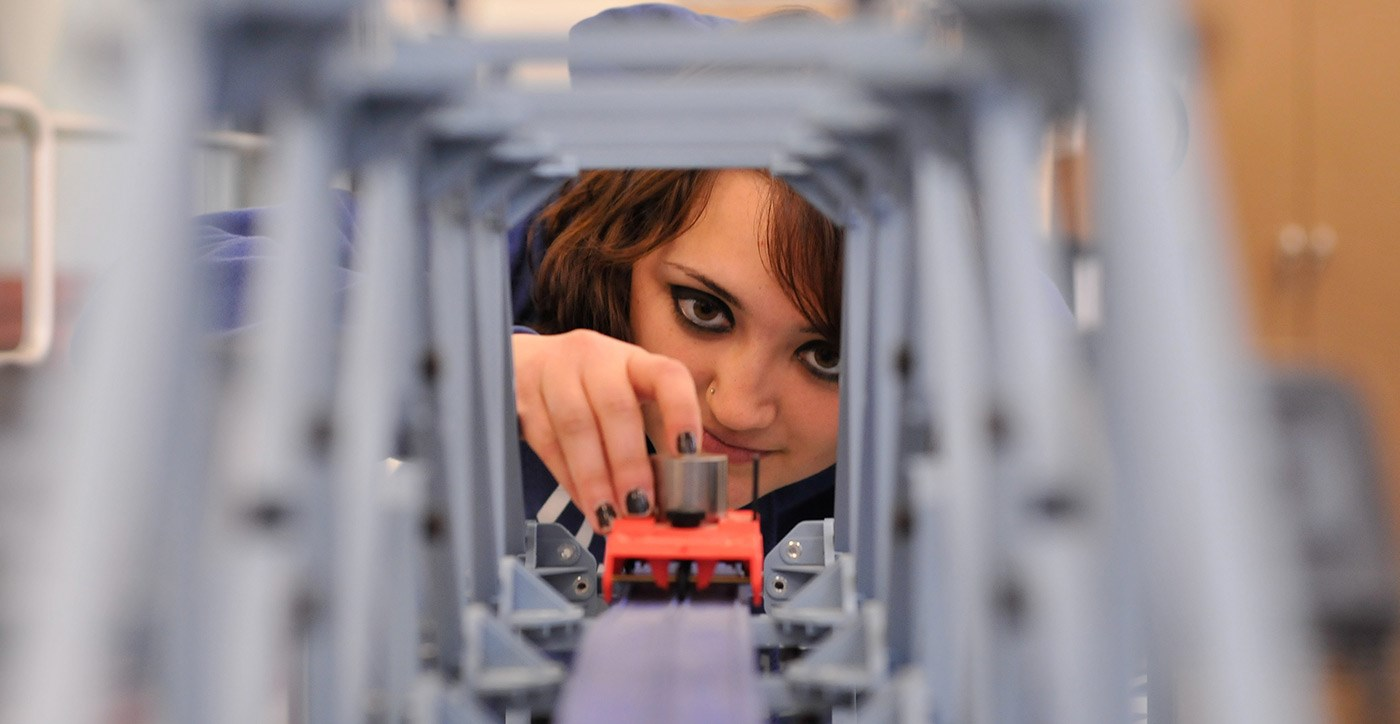 A female UMass Lowell student seen through the other side of a bridge model.