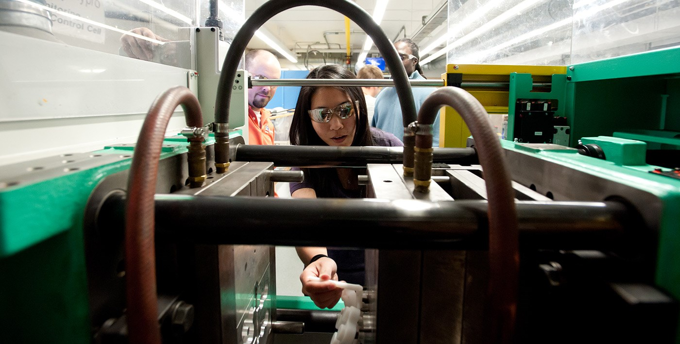 A female UMass Lowell student seen through machinery in a Plastics Engineering lab.