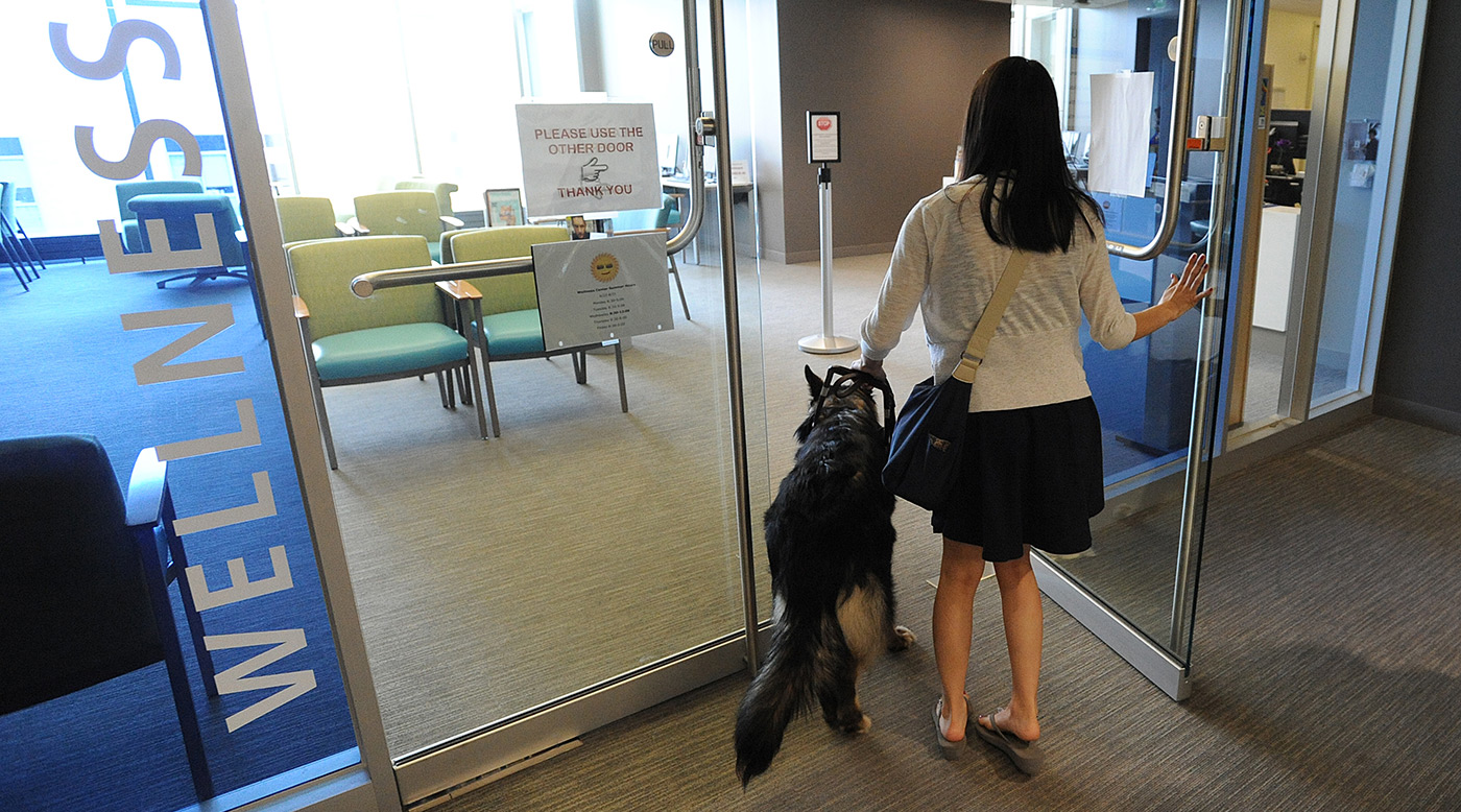A  a female student walking with her service dog into the Wellness Center.