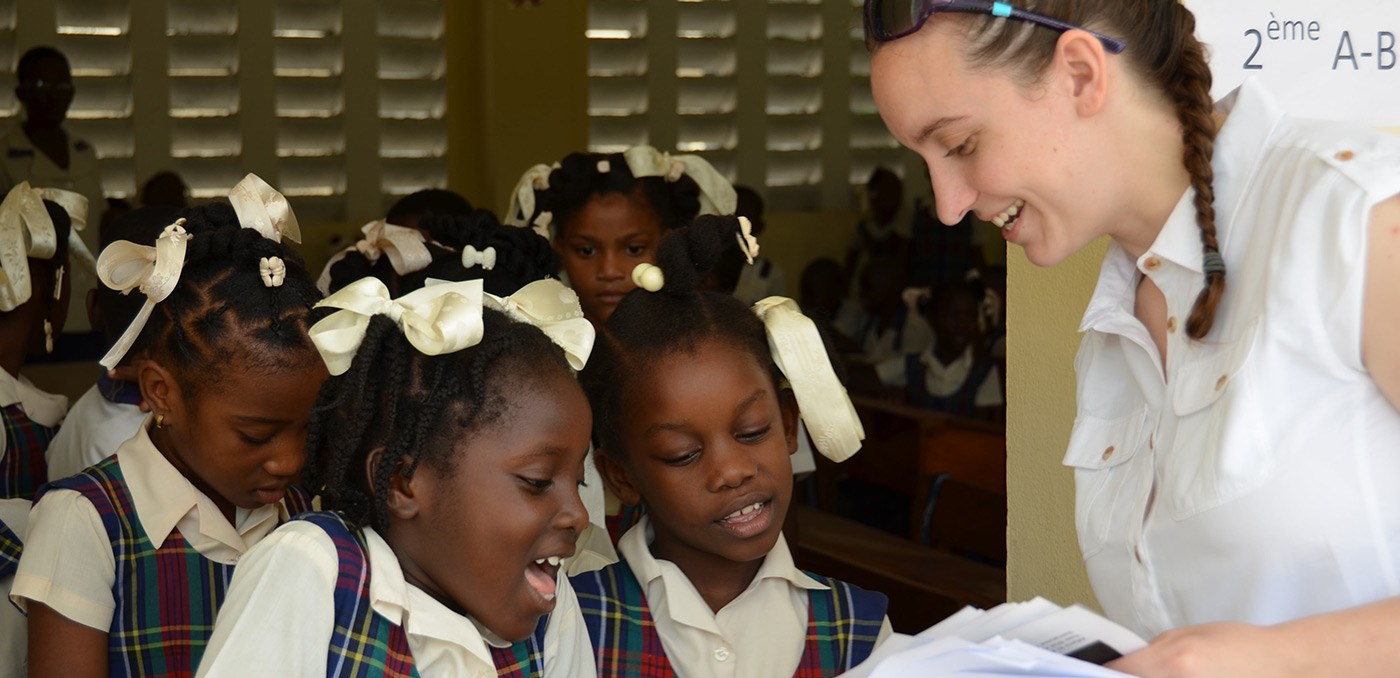A UMass Lowell female student showing papers of some kinds to several young female Haitian school children on a visit to Haiti in 2016.