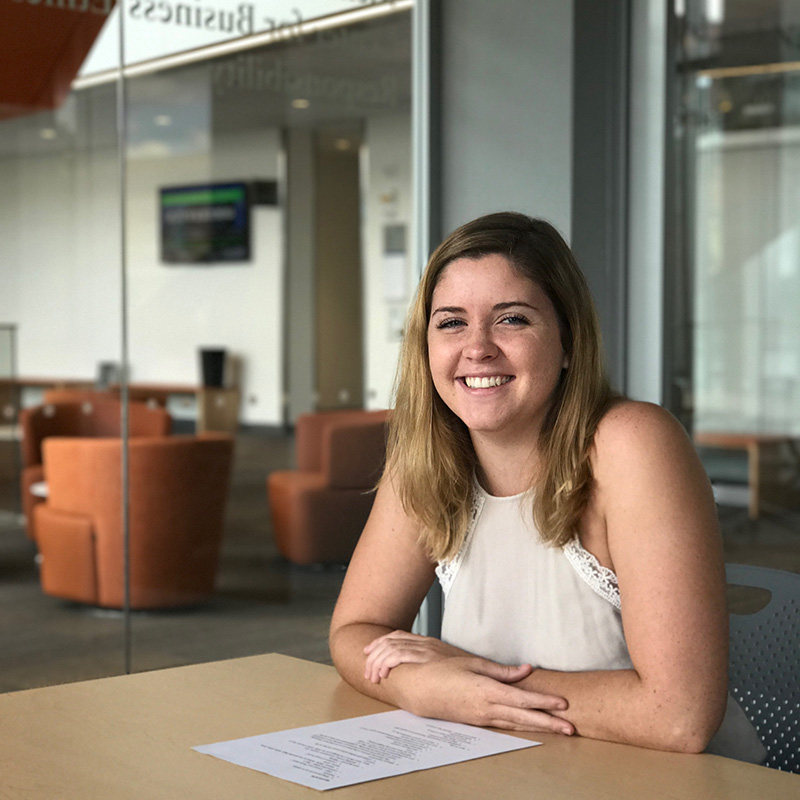 A smiling female student sitting at a table inside the Pulichino Tong Business Building at UMass Lowell. The Pulichino Tong Building will be at the heart of the North Campus Innovation District, which brings the university's engineering, science and business programs together for students, entrepreneurs and industry partners.