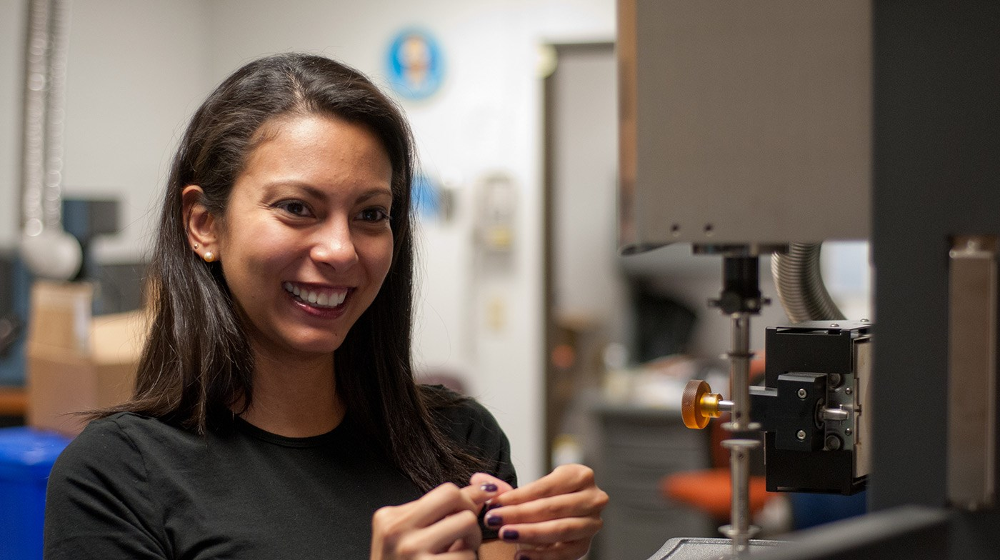 A female UMass Lowell student working in a Plastics Engineering lab and smiling.