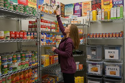A volunteer stocks the shelves at Navigators Food Pantry in University Crossing