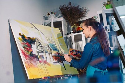 Woman painting picture in apartment