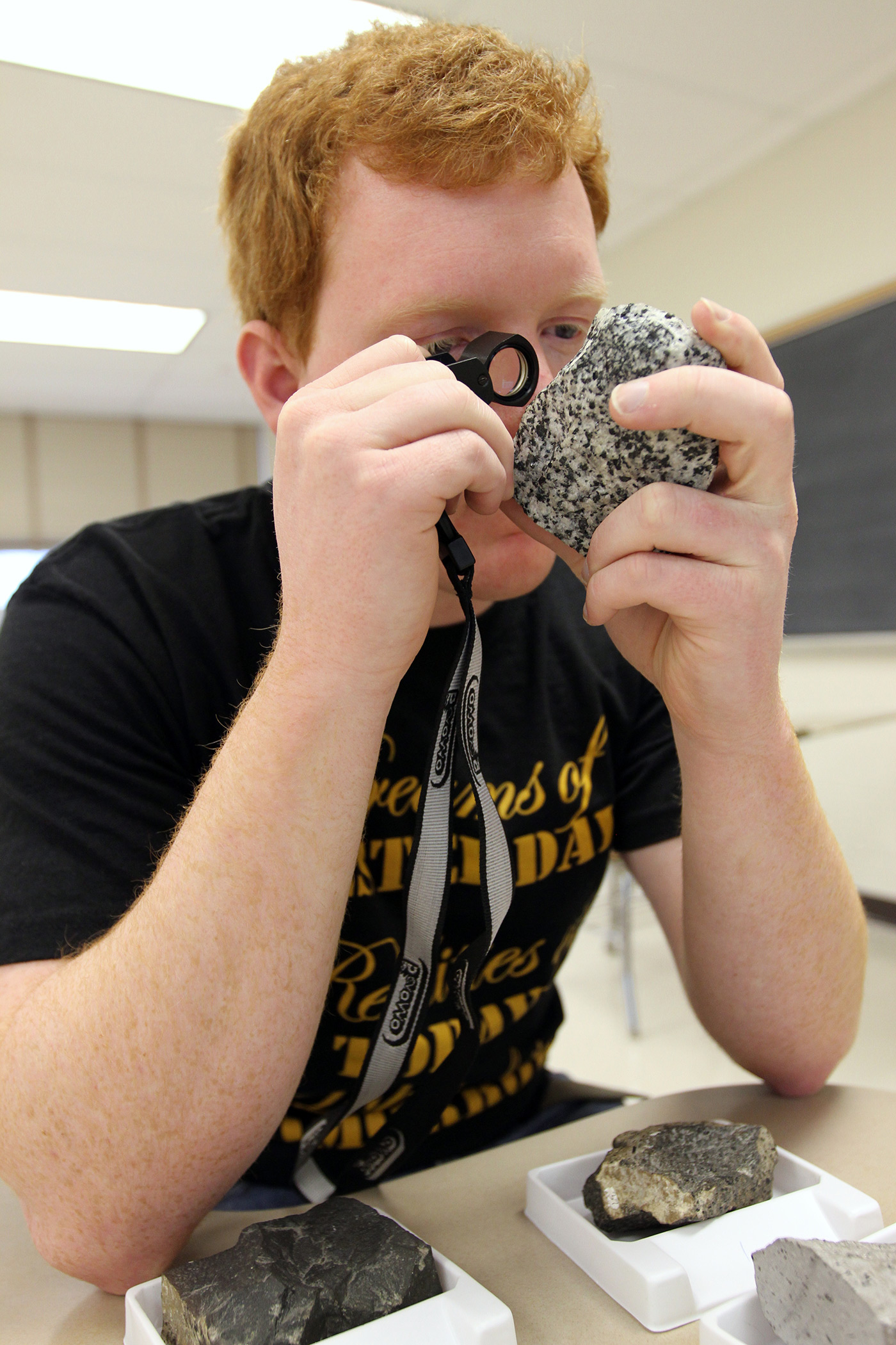 geology-male-student-magnifying-glass-rock