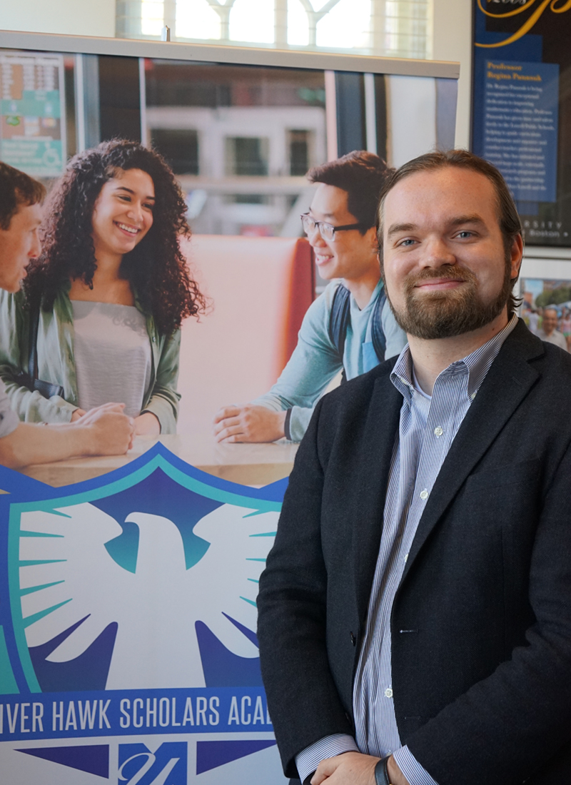 gerrit-boldt stading in front of a River Hawk Scholars Academy banner