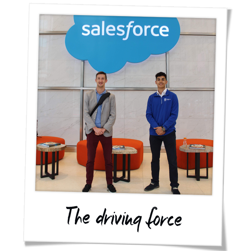 """Polaroid"" photo of Gianni Newman (right) and another Manning School of Business student in front of a Salesforce sign in Salesforce Tower in San Francisco - handwriting on the frame reads ""The driving force"""