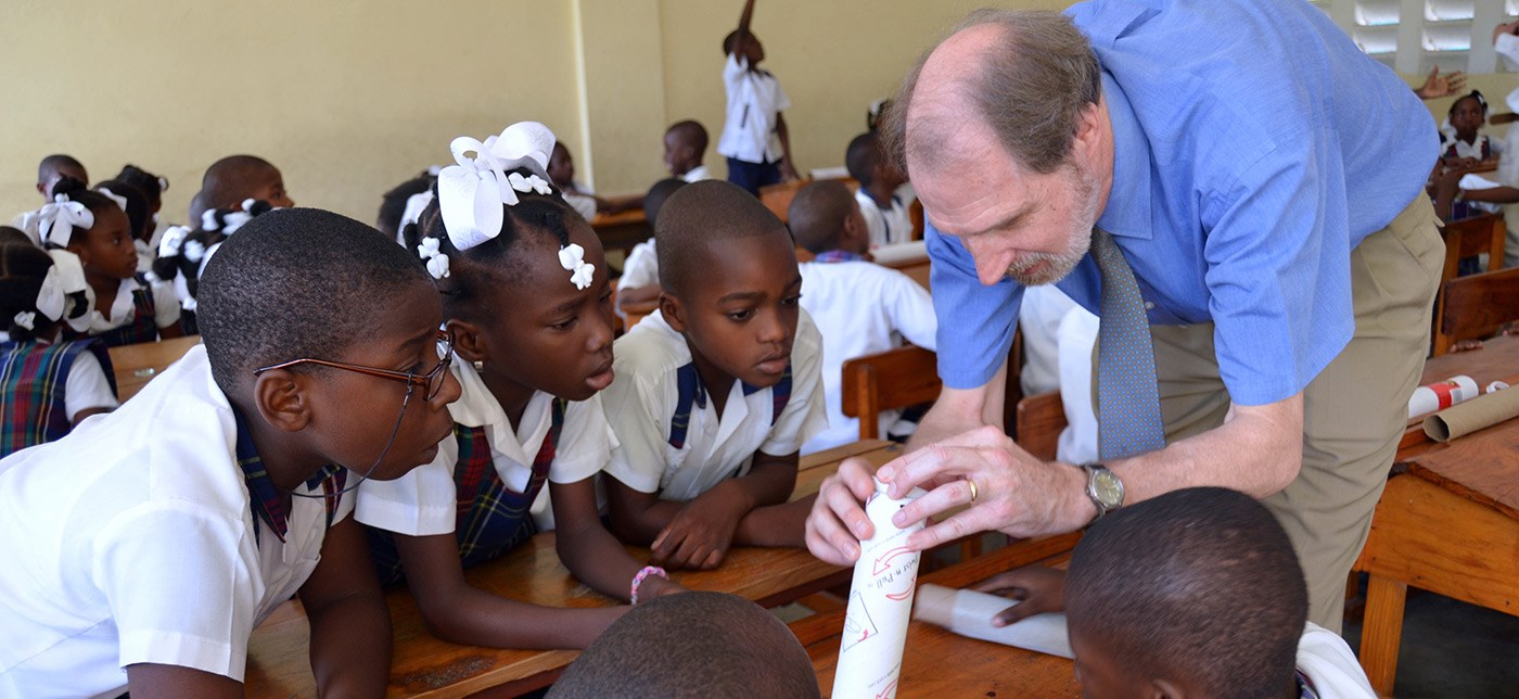 UMass Lowell Professor and Director of the Haiti Development Studies Center teaches schoolchildren in Les Cayes, Haiti, how to build a simple telescope out of cardboard tubes and lenses as part of the Haiti Development Studies Center's astronomy education outreach.